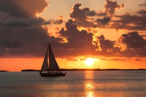 sail boat on calm water at sunset
